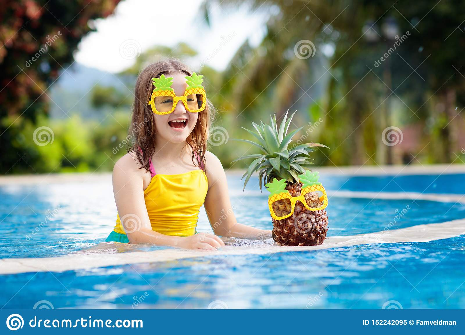 Child with pineapple in swimming pool. Kids swim