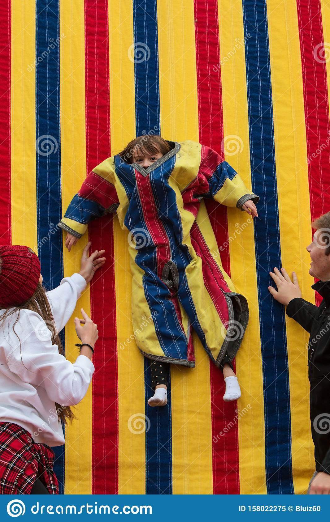 Child Wearing Velcro Suit Is Suspended Against Sticky Wall ...