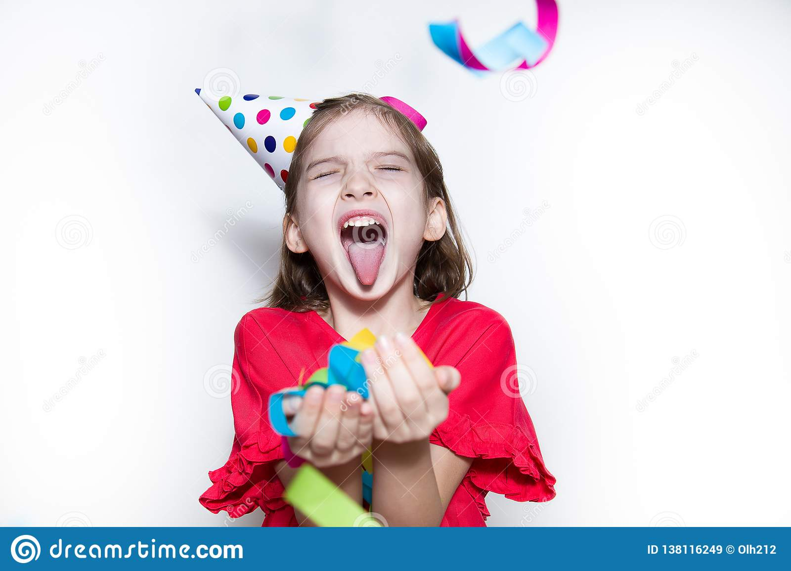 A child on a white background celebrates a bright event, wears a red dress and a cap.