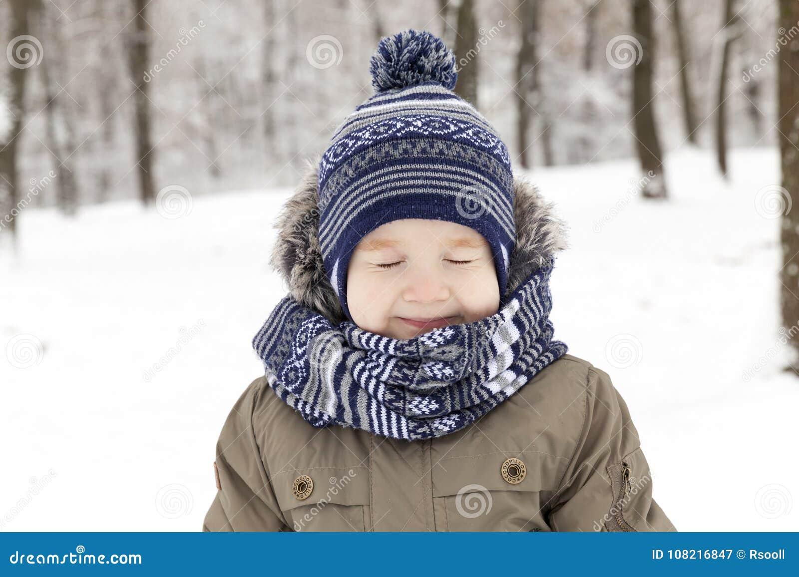 Child in winter, portrait squint blink