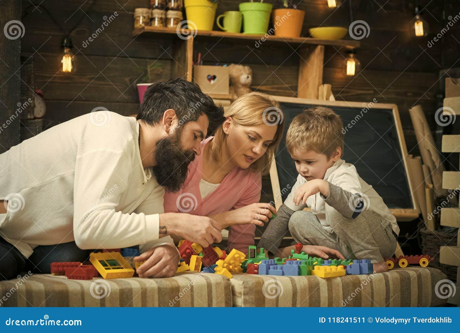 Childcare προσχολική εκπαίδευση Πατέρας, μητέρα και χαριτωμένο παιχνίδι γιων με τα τούβλα κατασκευαστών Η οικογένεια στο πολυάσχο