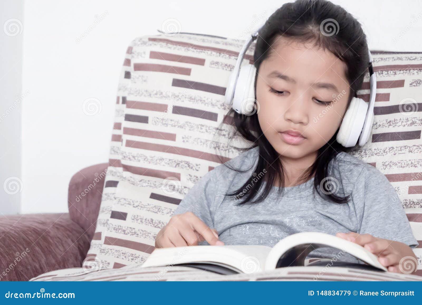 Childern die een boek op de bank lezen