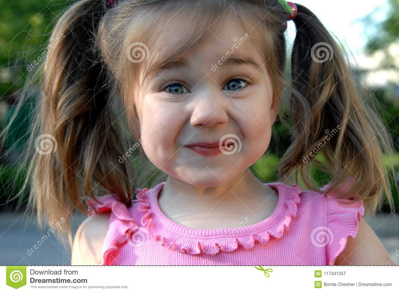 Little Girl Tries To Hold In Her Giggles As She Puts Face Into A Mirthful Smirk Has Pigtails And Pink Shirt
