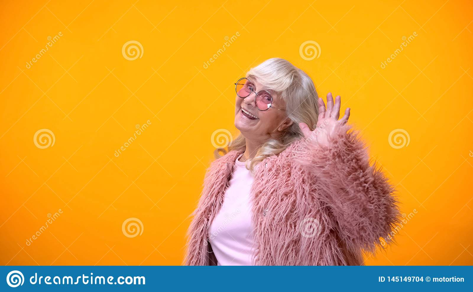Childish elderly woman in pink coat and round sunglasses smiling into camera