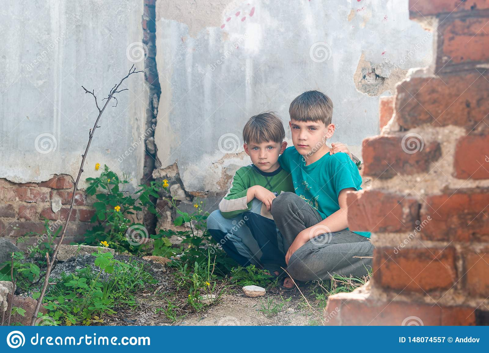 Children in an abandoned house, two poor abandoned boys, orphans as a result of natural disasters and military actions. Submission