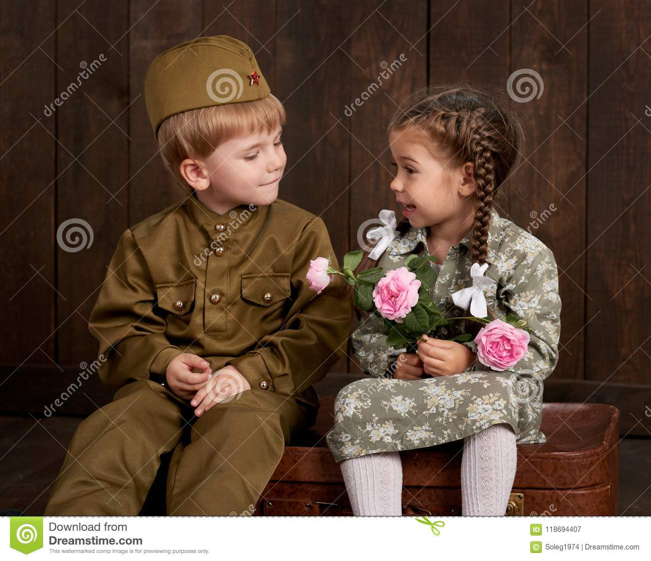 Children boy are dressed as soldier in retro military uniforms and girl in pink dress sitting on old suitcase, dark wood backgroun