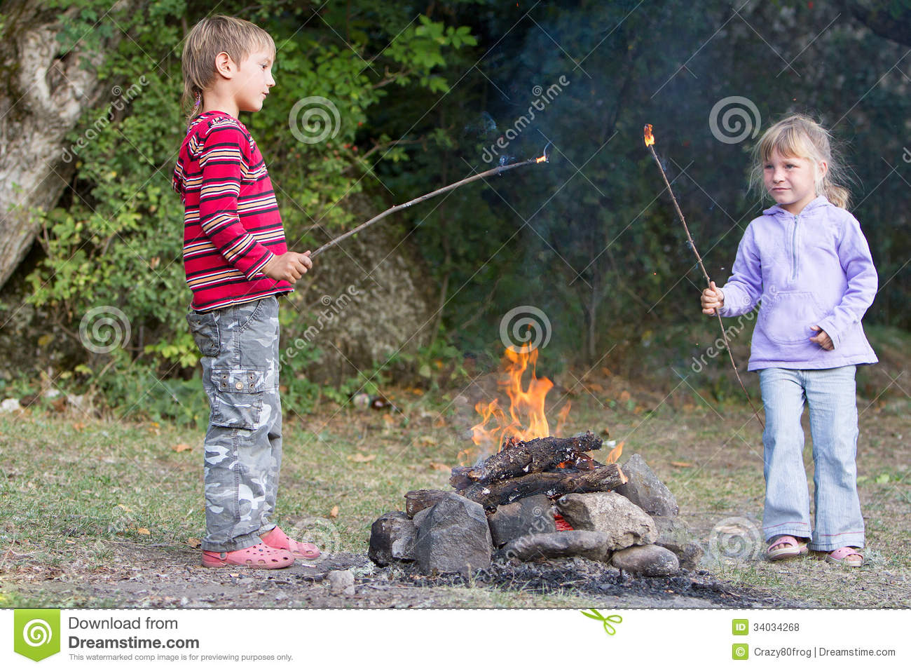 Children Boy And Girl Playing With Fire On Natural Backgroun