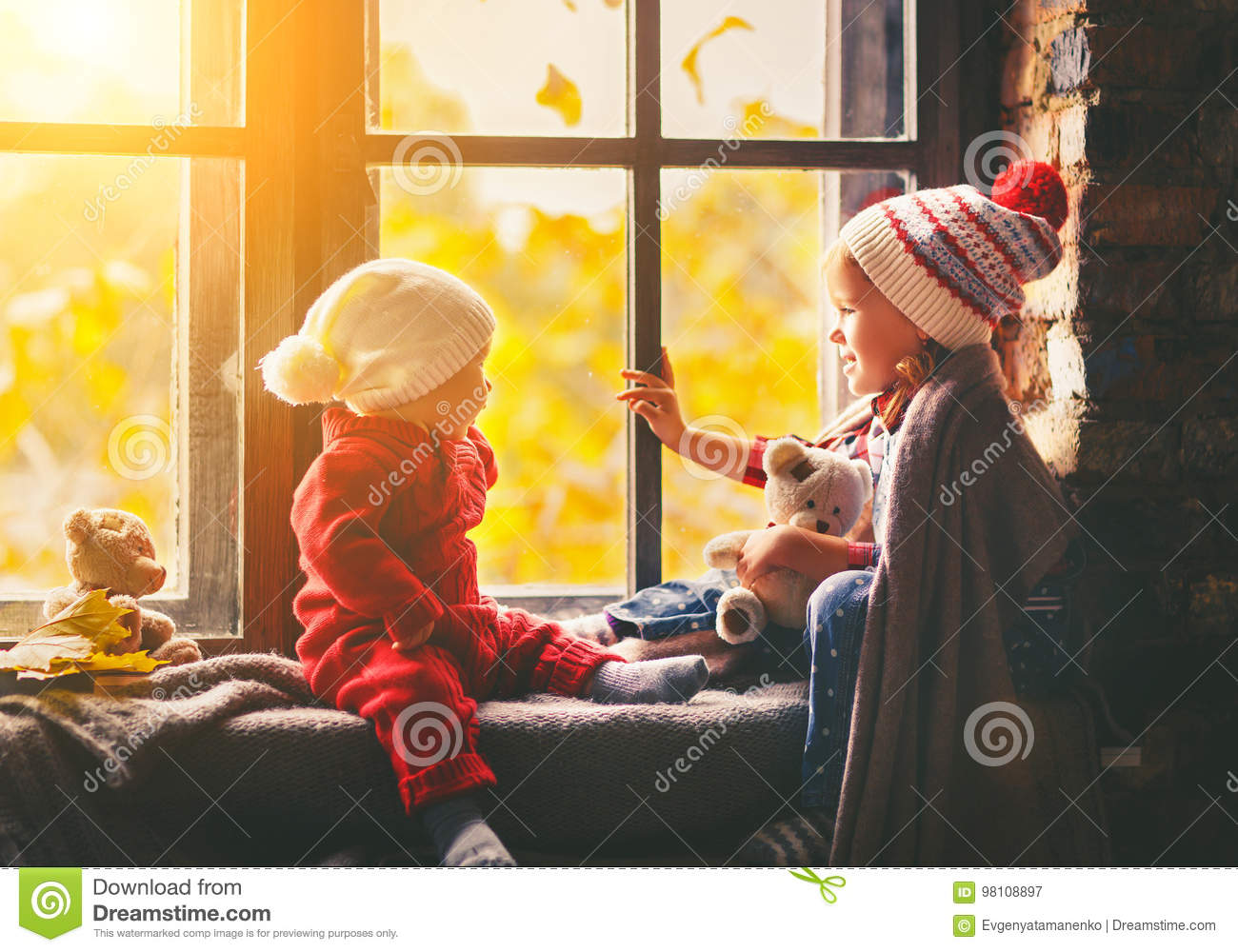 Children brother and sister admiring window for autumn