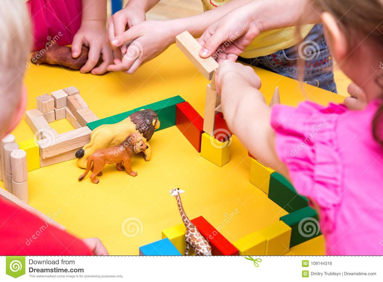 Children Build A Zoo Of Wooden Bricks On Table Stock Photo - Image