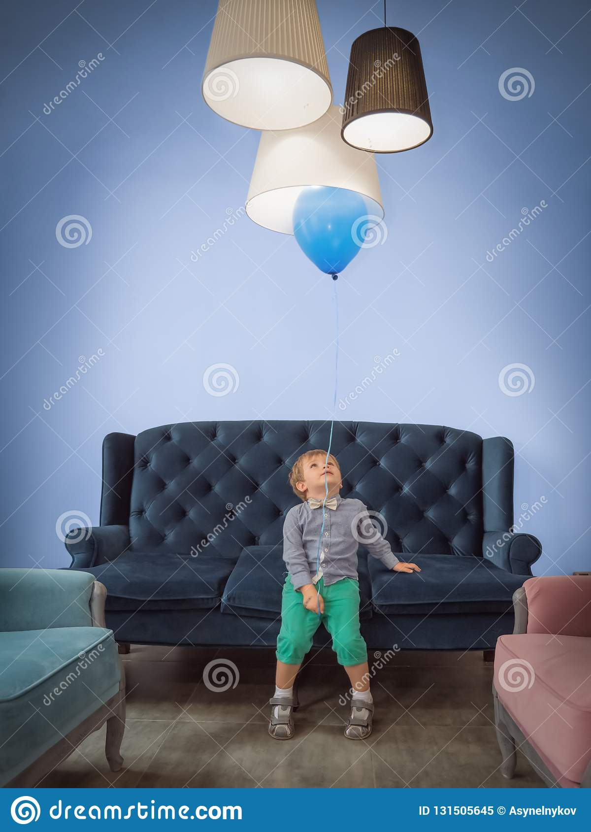 Children celebration background. Happy childhood concept. Cute boy with balloon having fun at home.