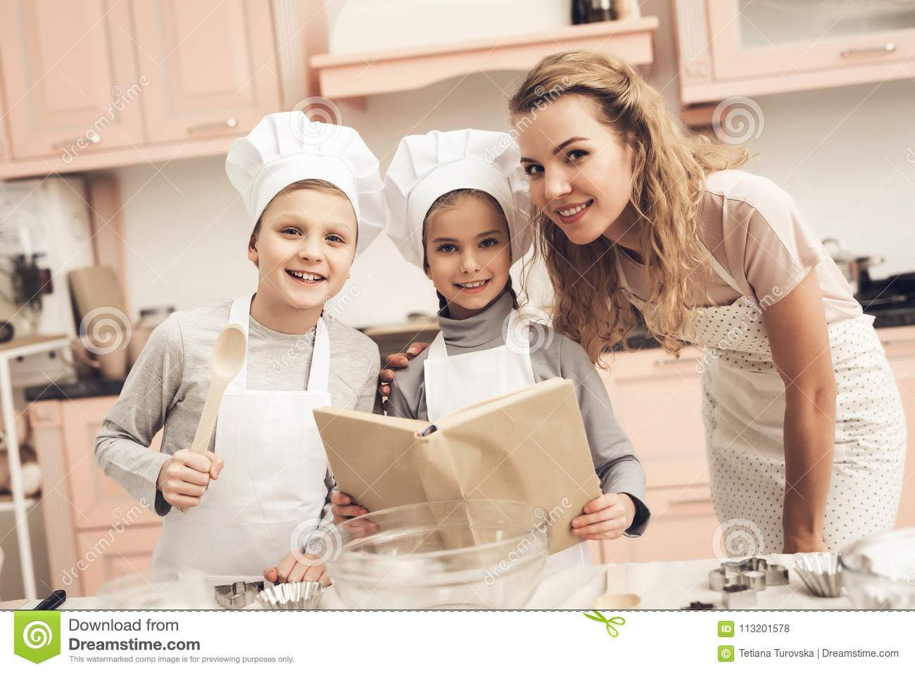 Children with mother in kitchen. Family is reading recipe in cookbook.