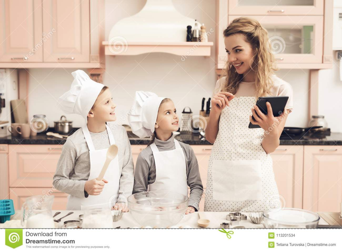 Children With Mother In Kitchen  Family Is Reading Recipe On