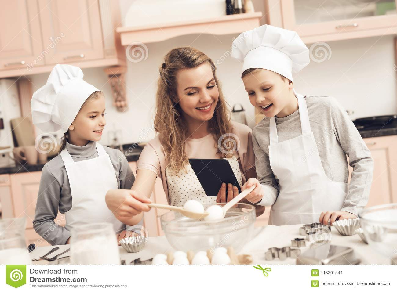 Children with mother in kitchen. Family is reading recipe on tablet.