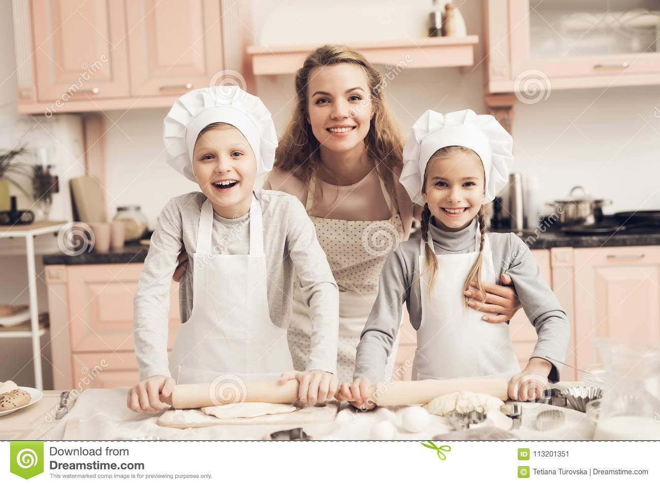 Children with mother in kitchen. Family is ready to roll out dough.