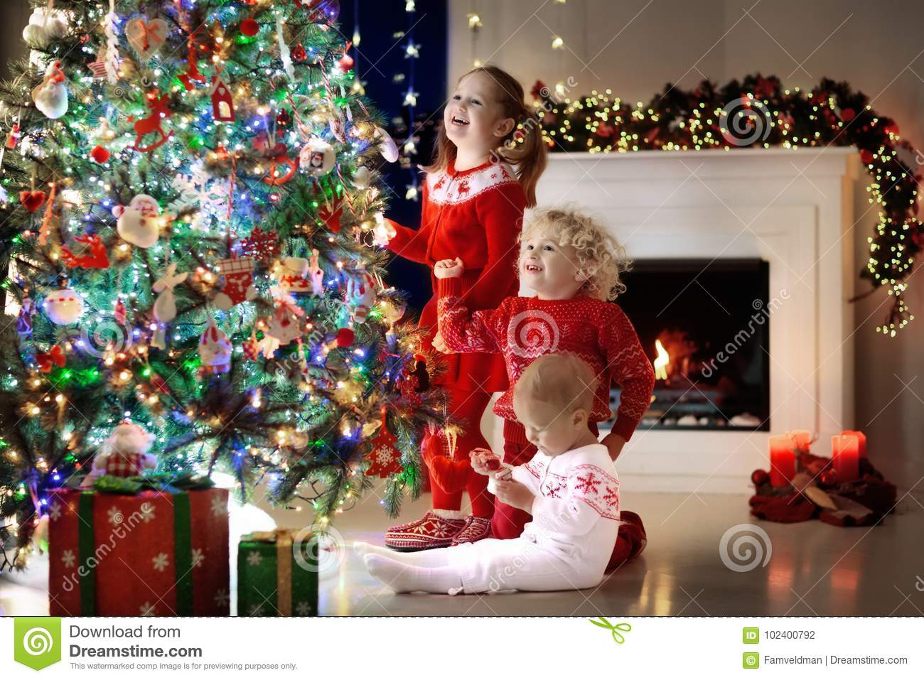 Children at Christmas tree. Kids at fireplace on Xmas eve