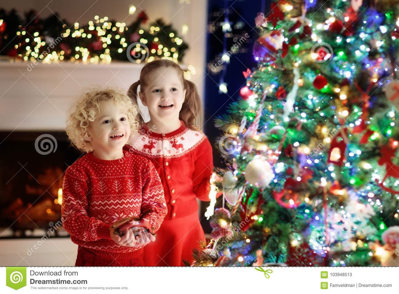 Children At Christmas Tree. Kids At Fireplace On Xmas Eve Stock ...