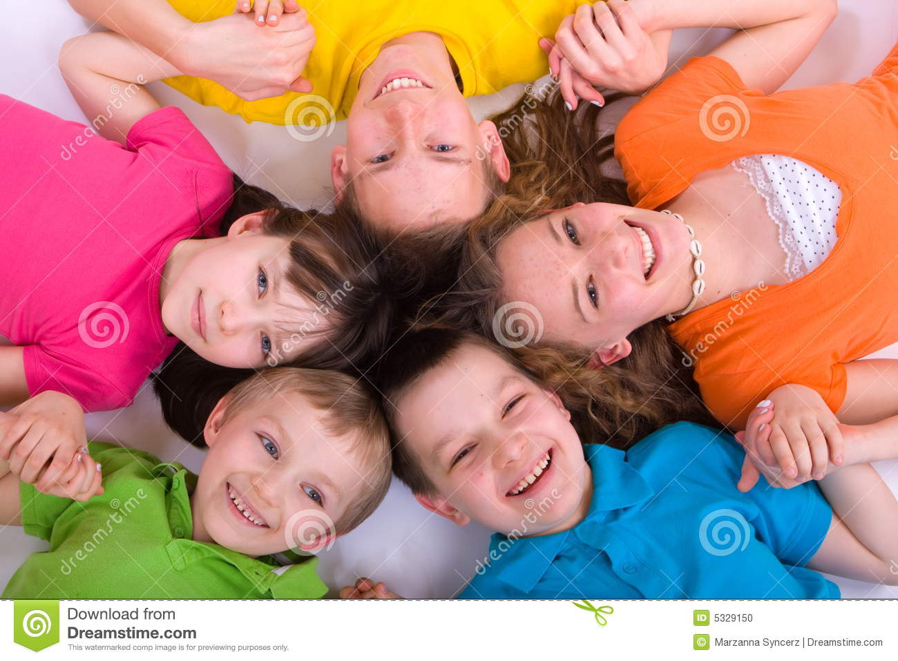 Five smiling children holding hands laying in a circle with their