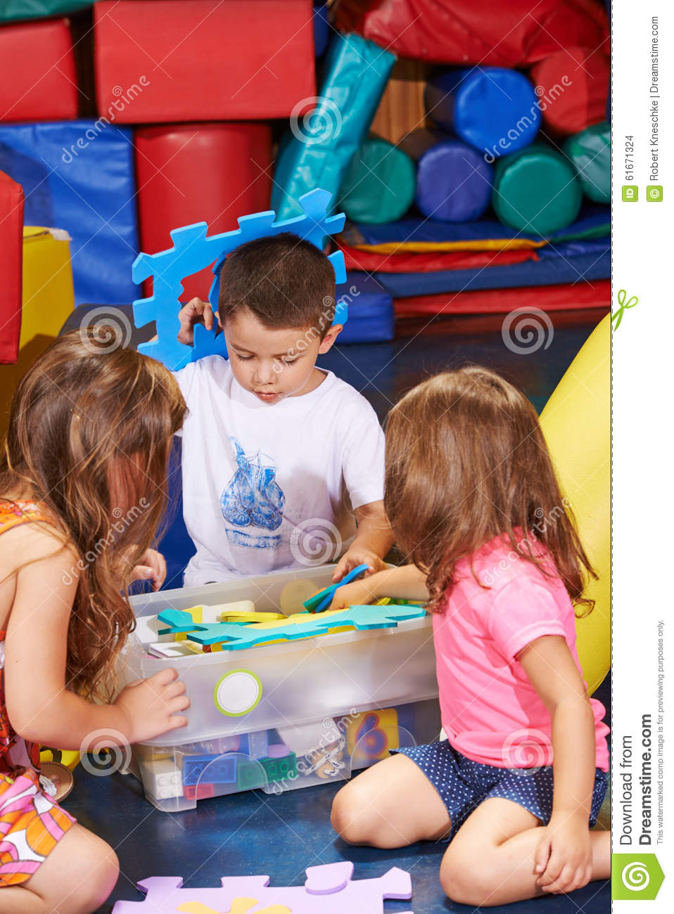 Children Cleaning Up Toys In Box Stock Photo - Image: 61671324