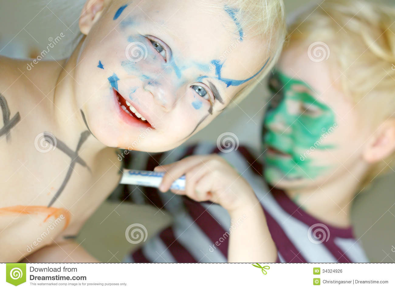 Children Coloring Their Faces With Markers Stock Photo