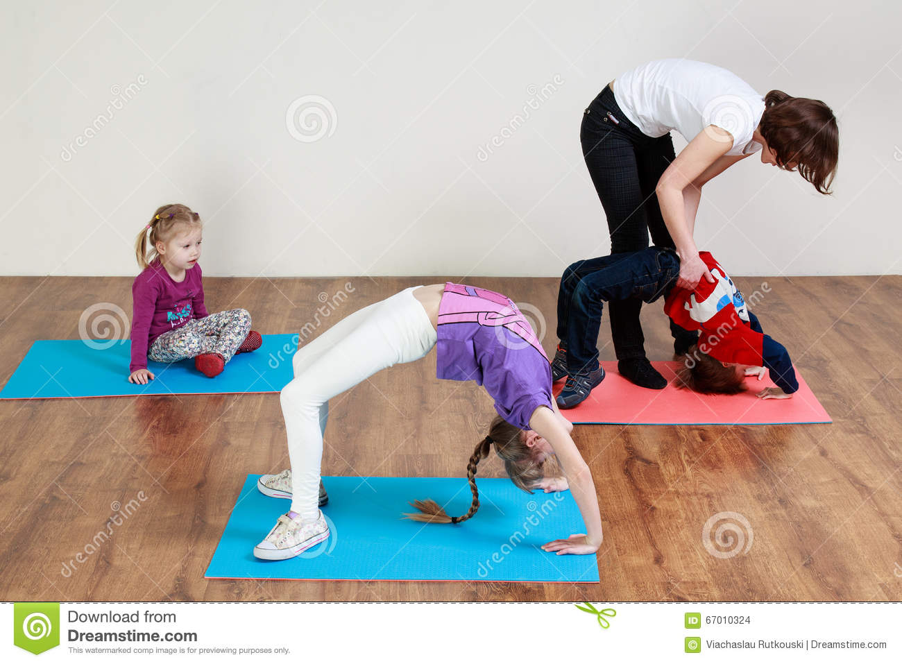 Children are doing a bridge exercise with the help of a trainer