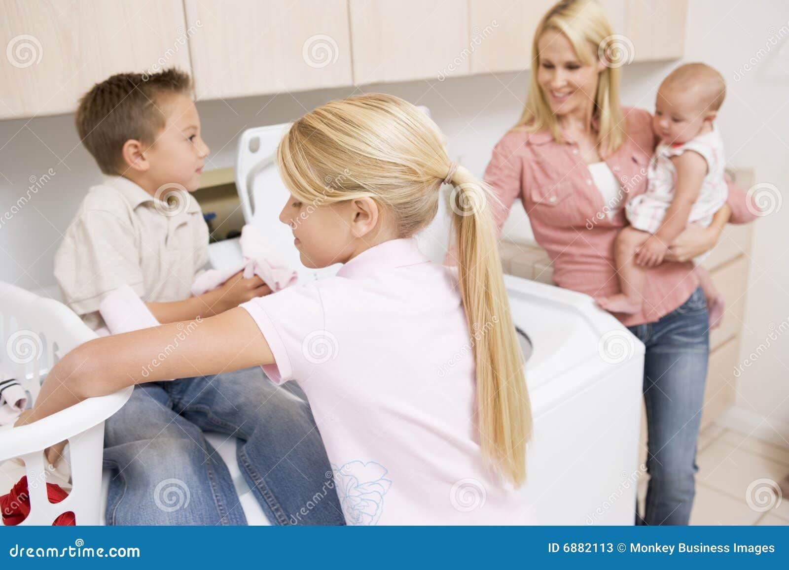 Children doing laundry mother