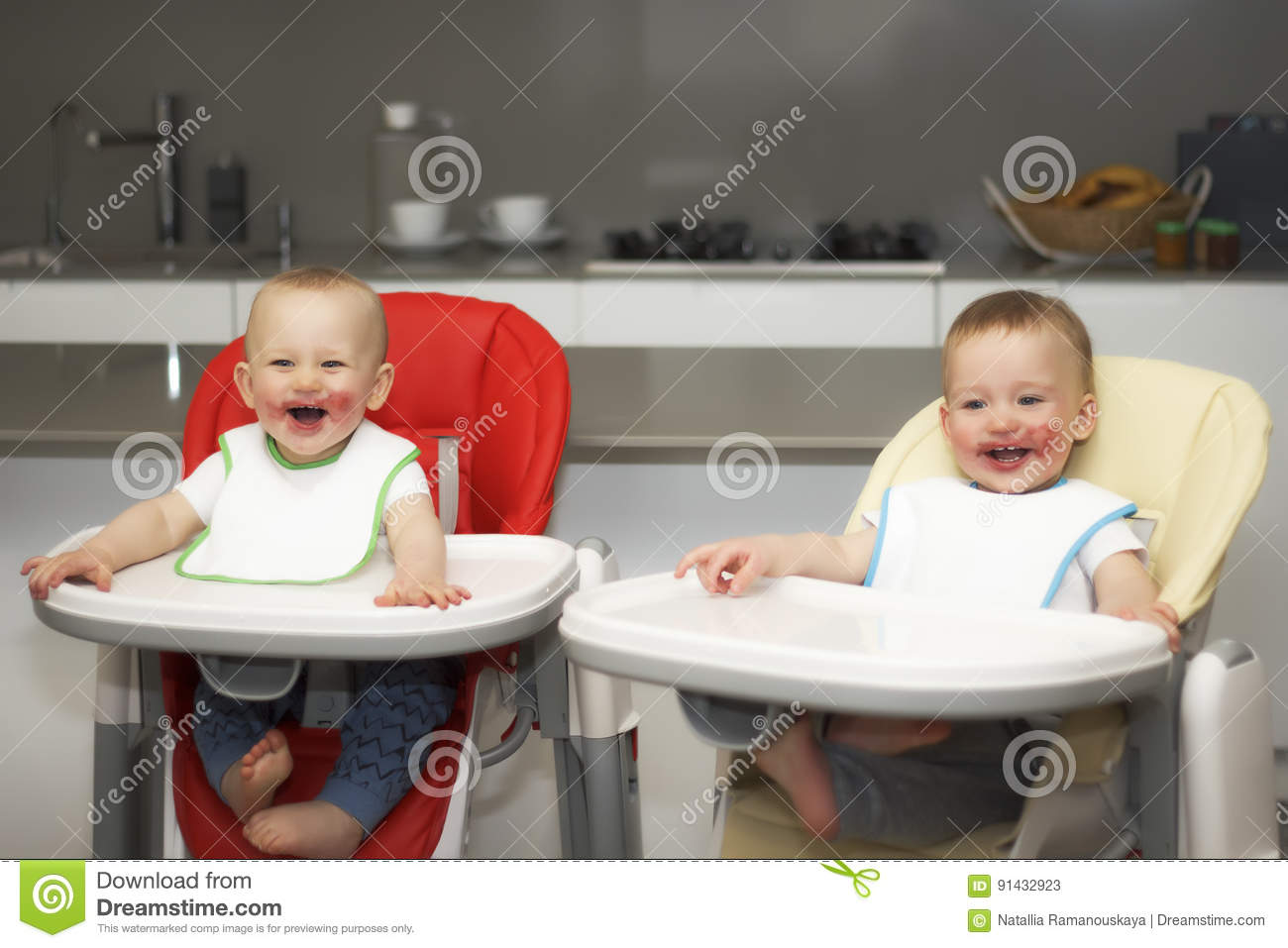 Children eat blueberries in a high baby chair. The boys have a dirty face
