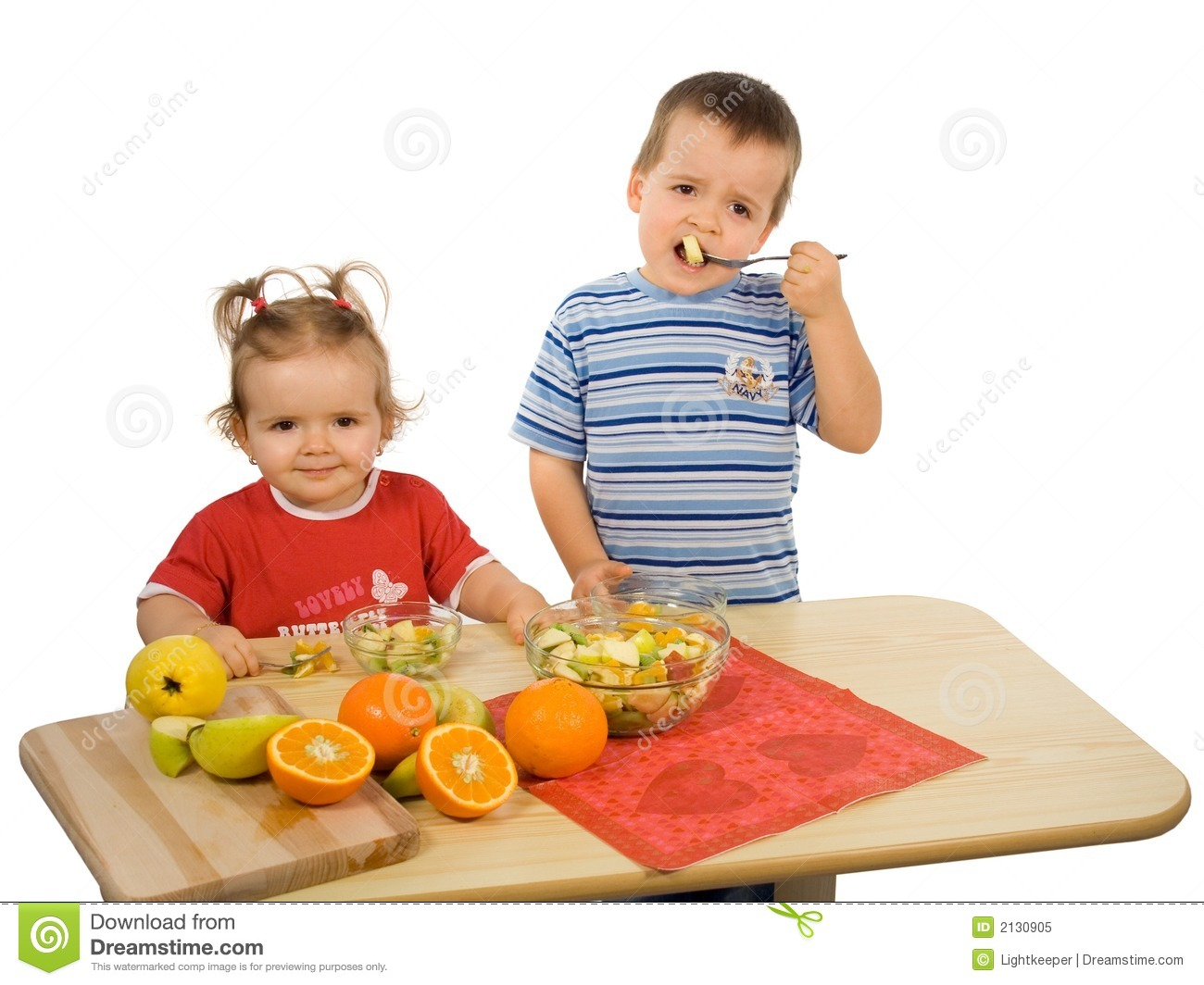 Children, girl and boy, eating fruit salad (isolated).