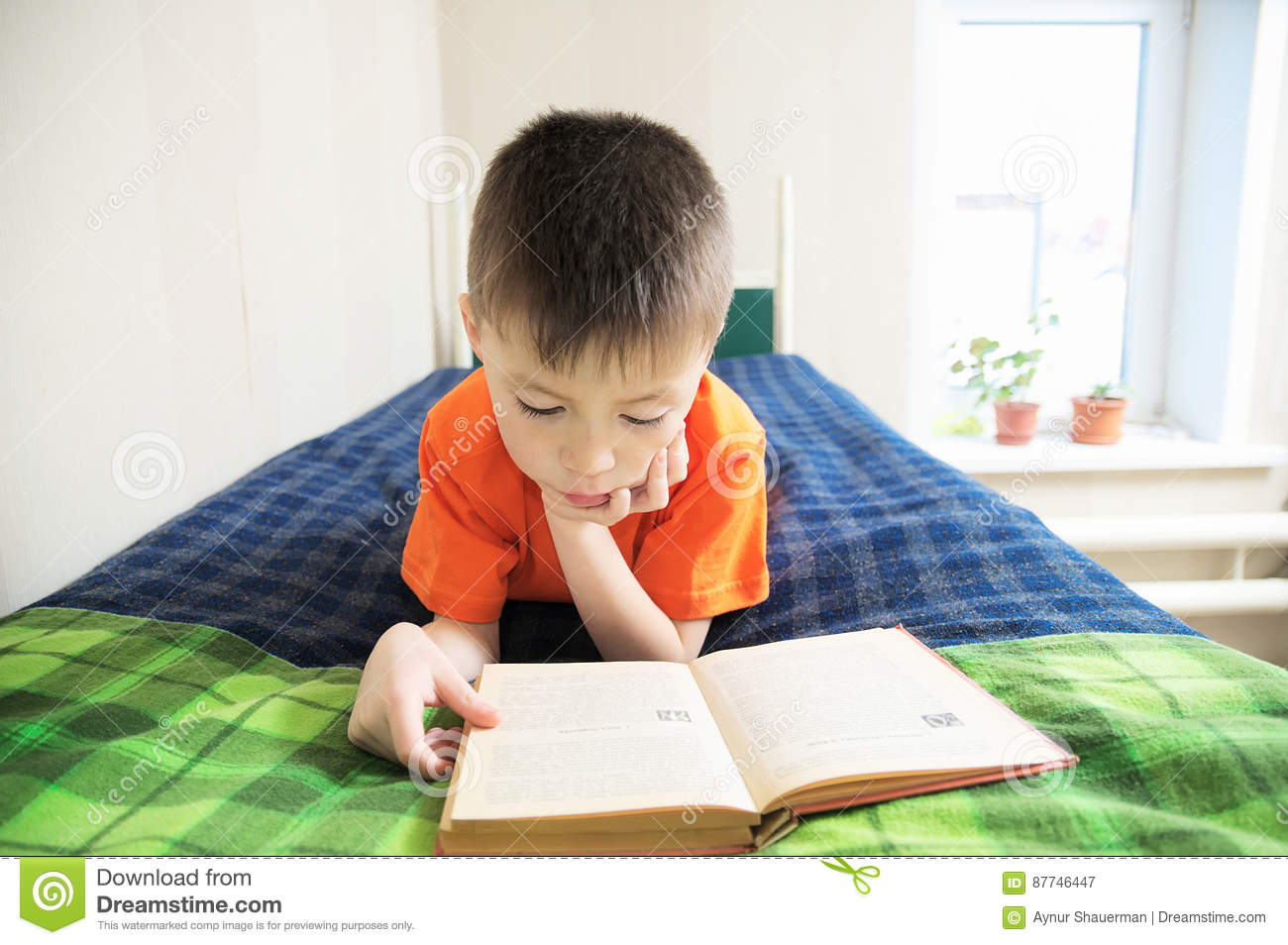 Children education, boy reading book lying on bed, child portrait smiling with book, interesting storybook