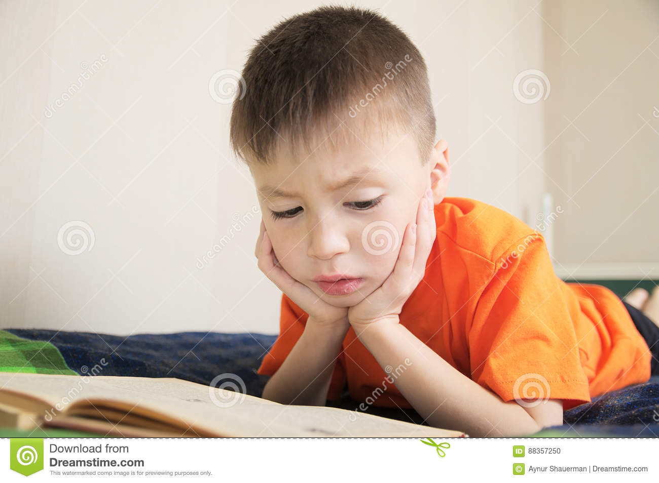 Children education, child reading book lying on bed, boy portrait with book, interesting storybook