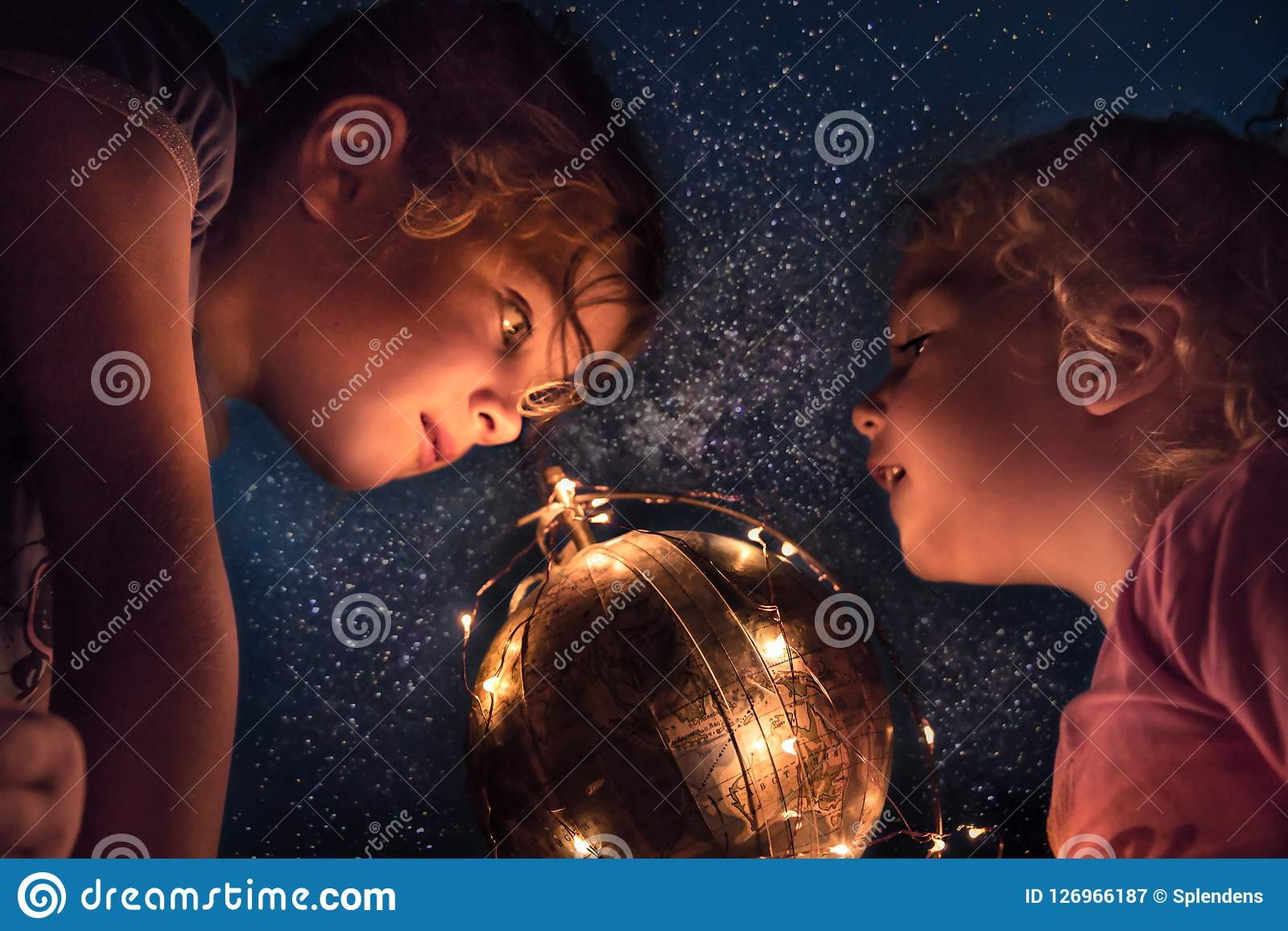 Children exploring night sky with space stars and earth planet concept astronomy and discovery