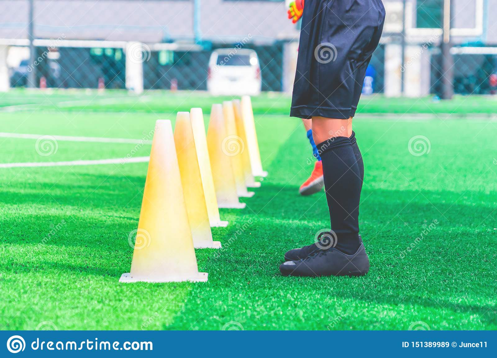 Children with soccer boots training on training cone on soccer ground