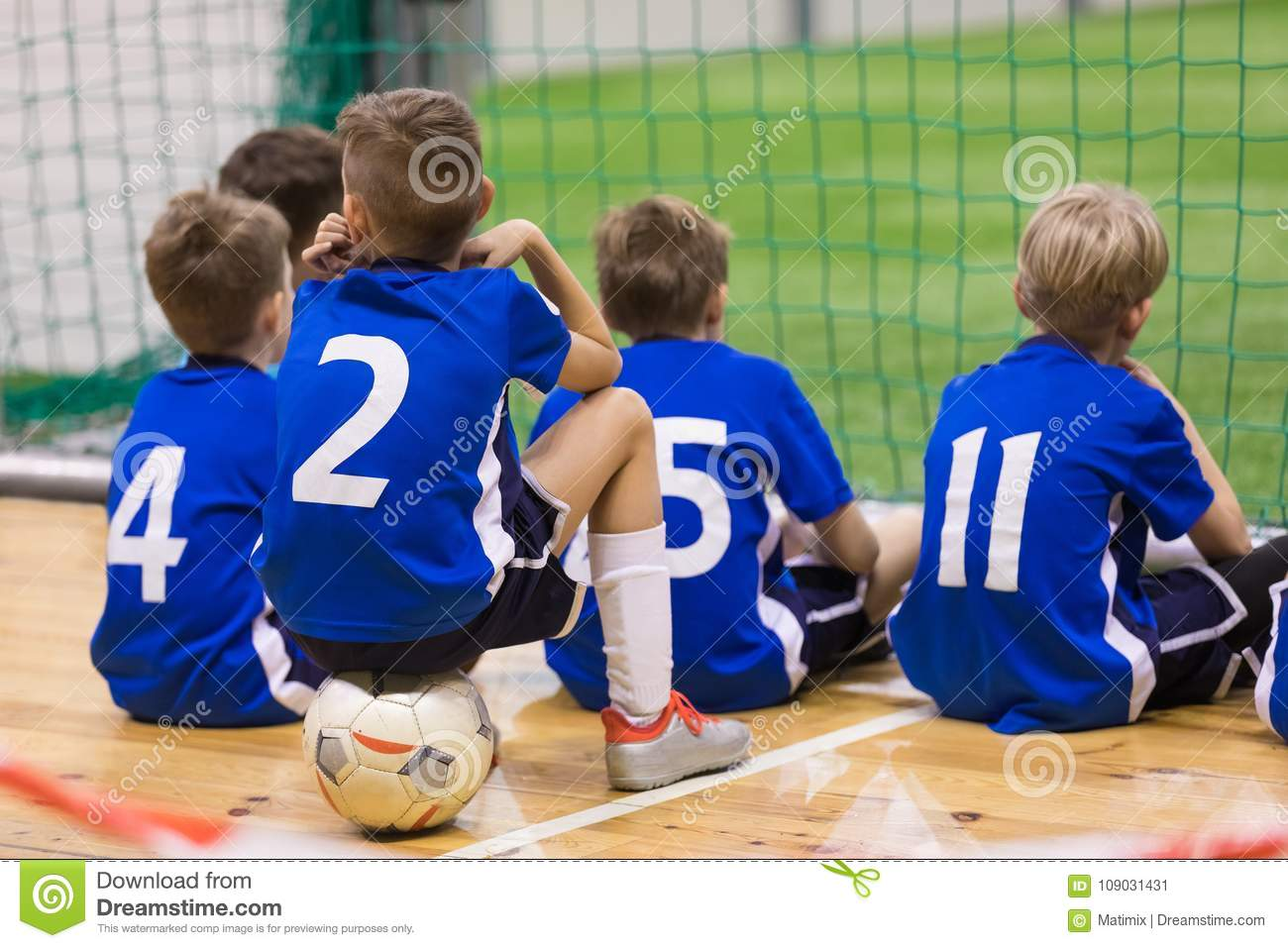 a3a47a973 Children futsal team. Group of young indoor soccer players sitting together.