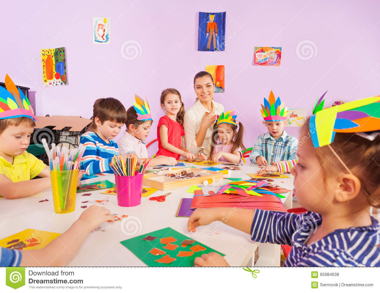 Children Glue Paper Crafts Together With Teacher Stock Photo Image