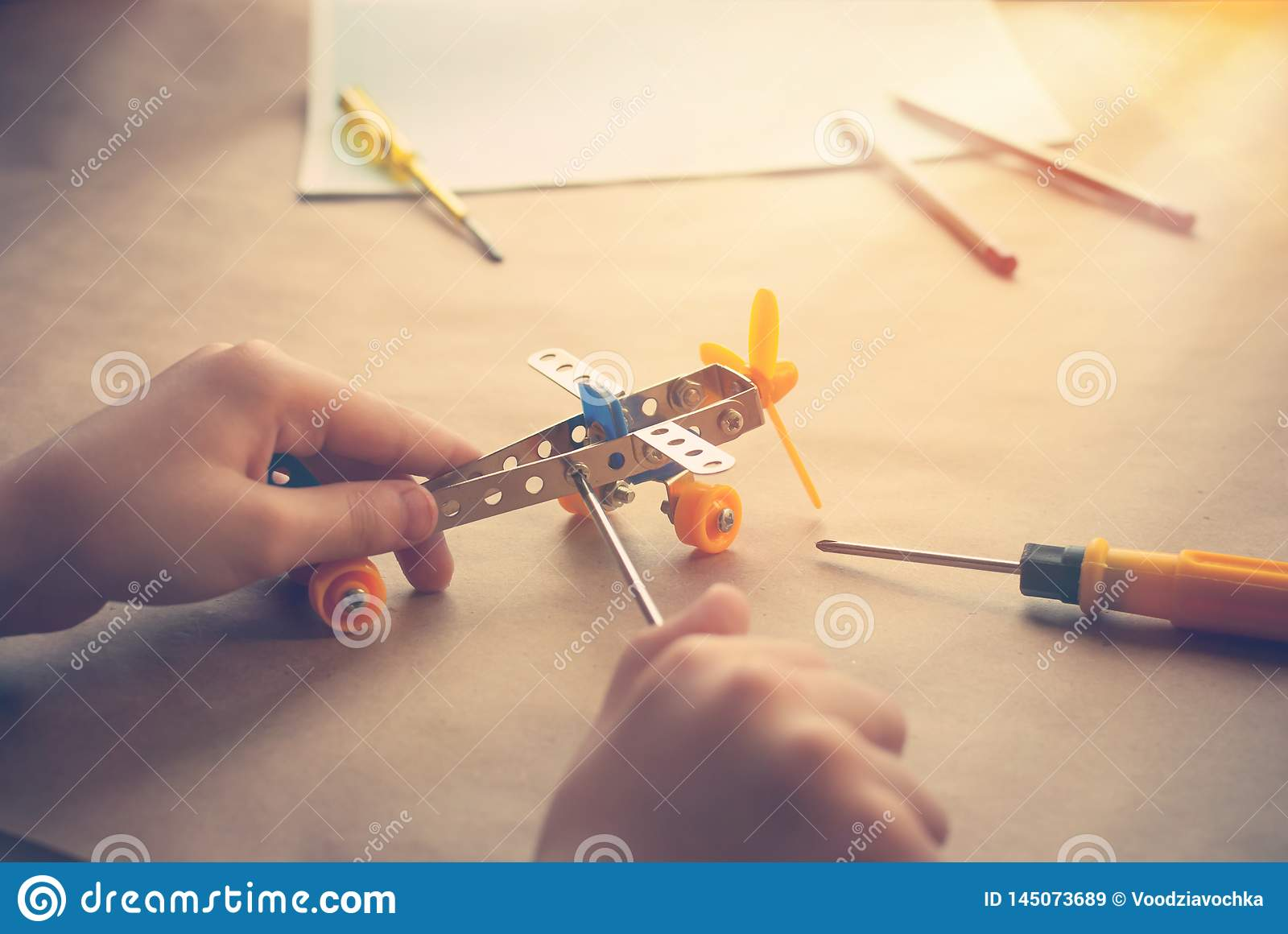 Children hands with Toy iron plane. Metal constructor with screwdrivers. Dream, play and create