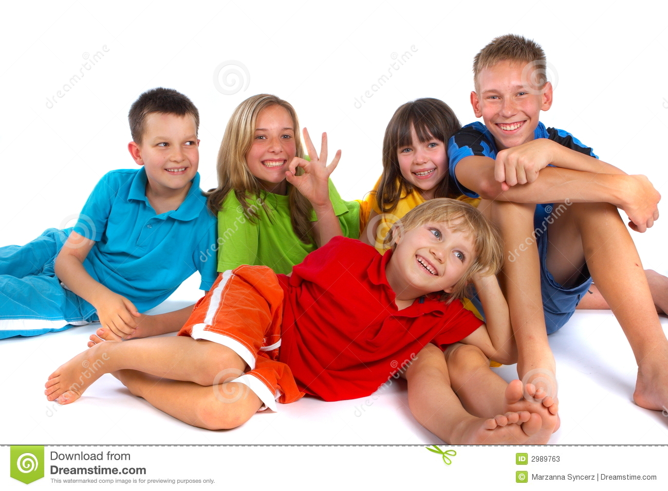 group of children having fun while posing together in a studio.