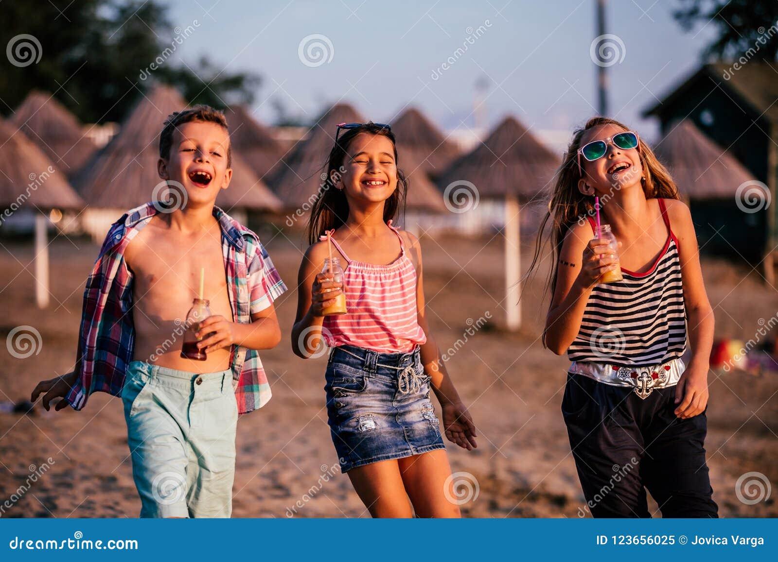 Children having fun while walking along a sandy beach
