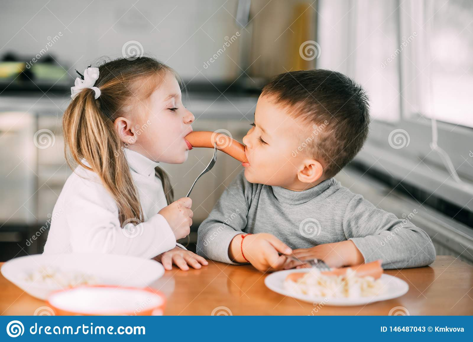 Children In The Kitchen Boy And Girl Eat Sausages With Pasta Very Fun And Together Share One Stock Image Image Of Face Love 146487043