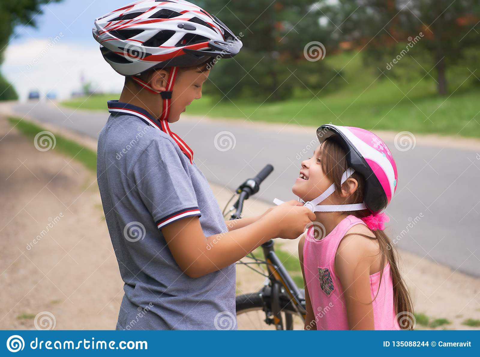 Children learn to ride bicycle in a park on summer day. Teenager boy helping preschooler girl to put on safety helmet