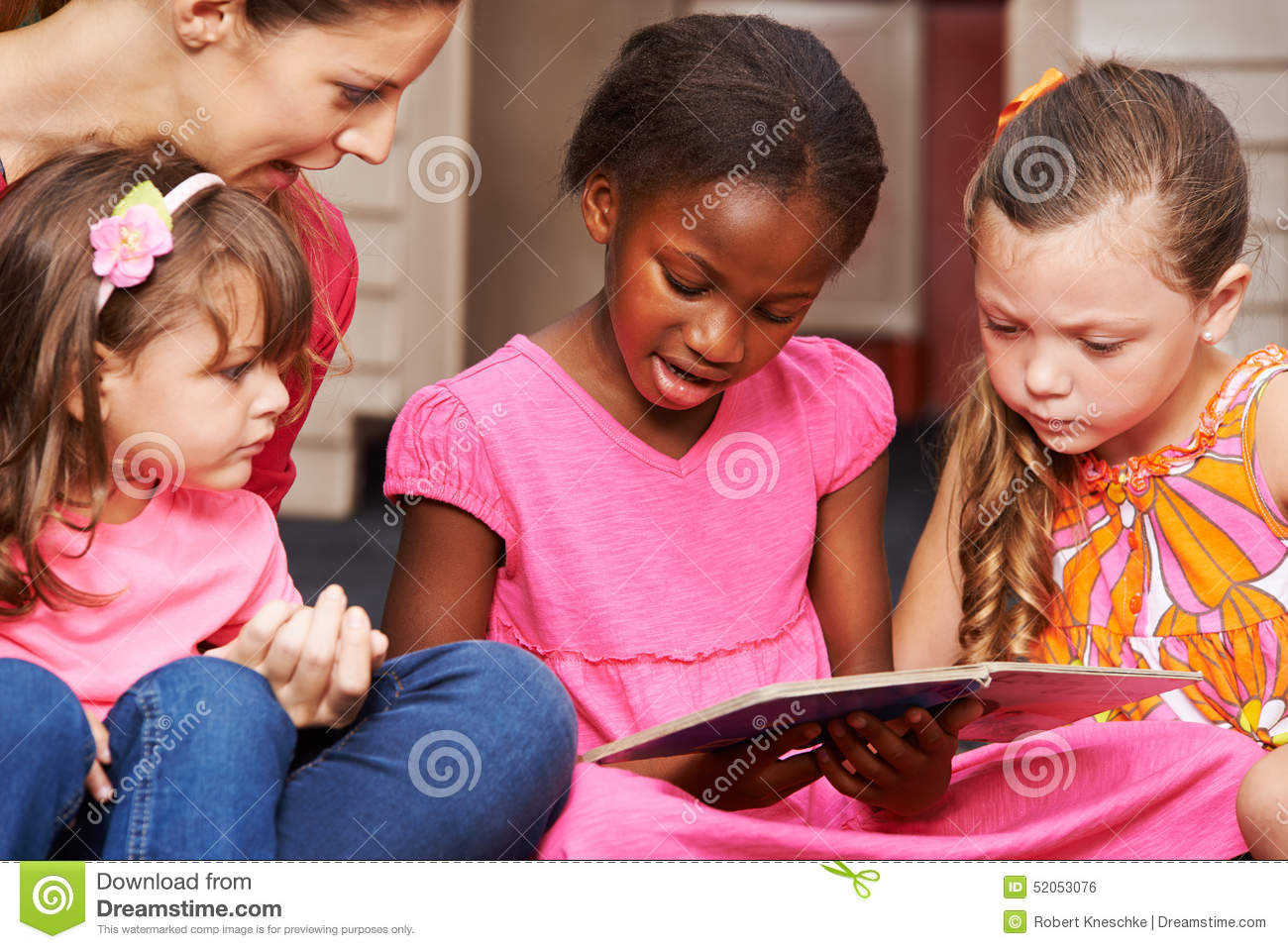 Download Children Learning To Read With Nursery Teacher Stock Photo