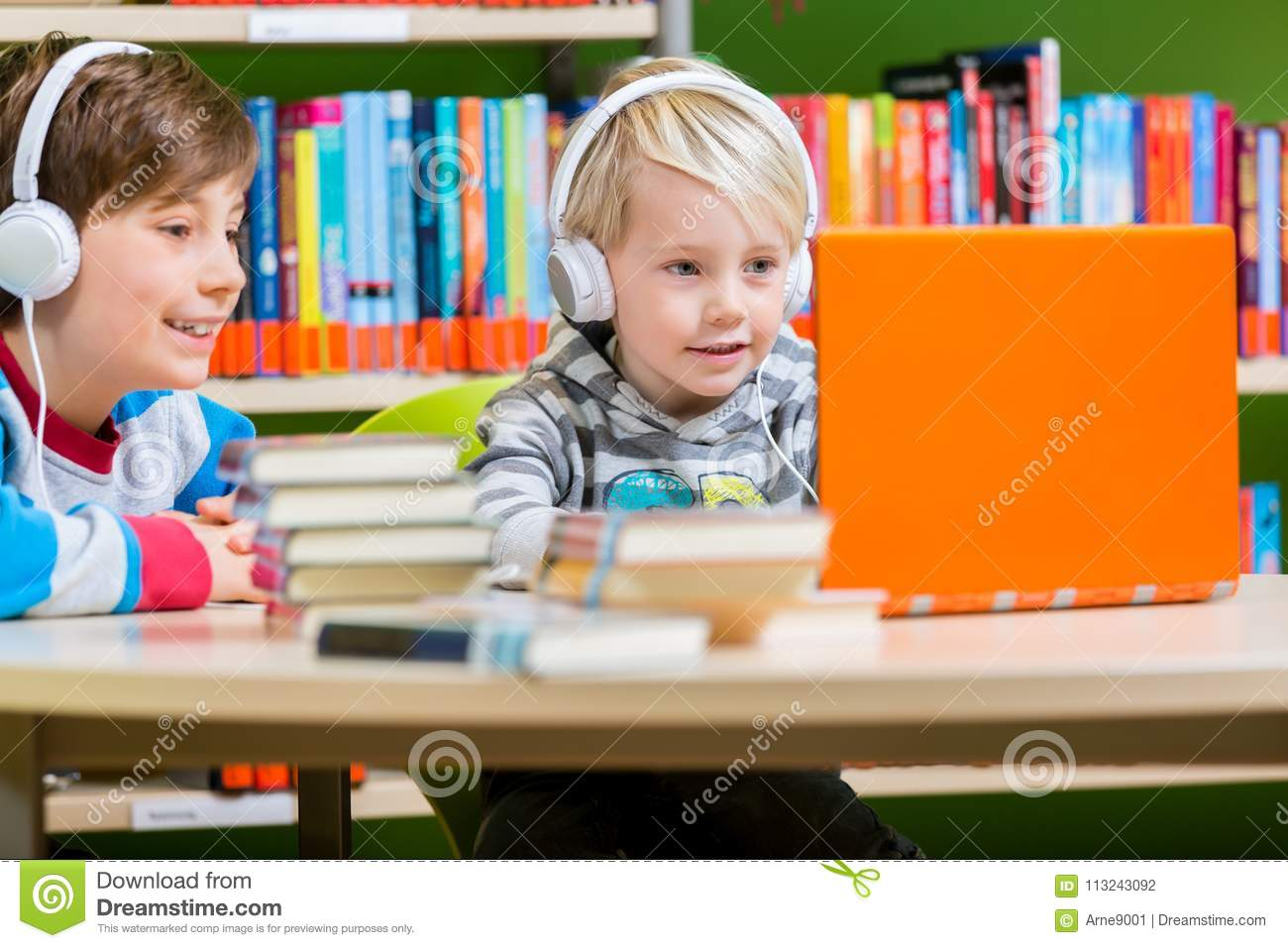 Children in a library listening to audio books
