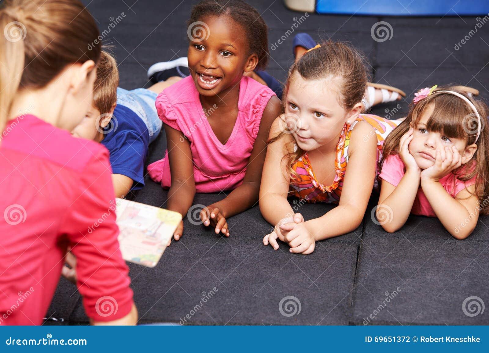 Children Listening To Fairytale Book In Preschool Stock