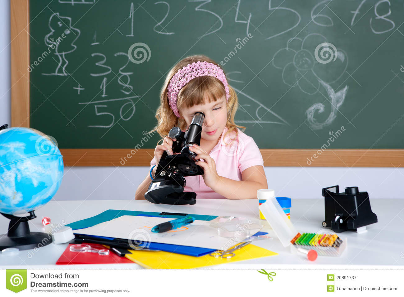 Children little girl at school with microscope