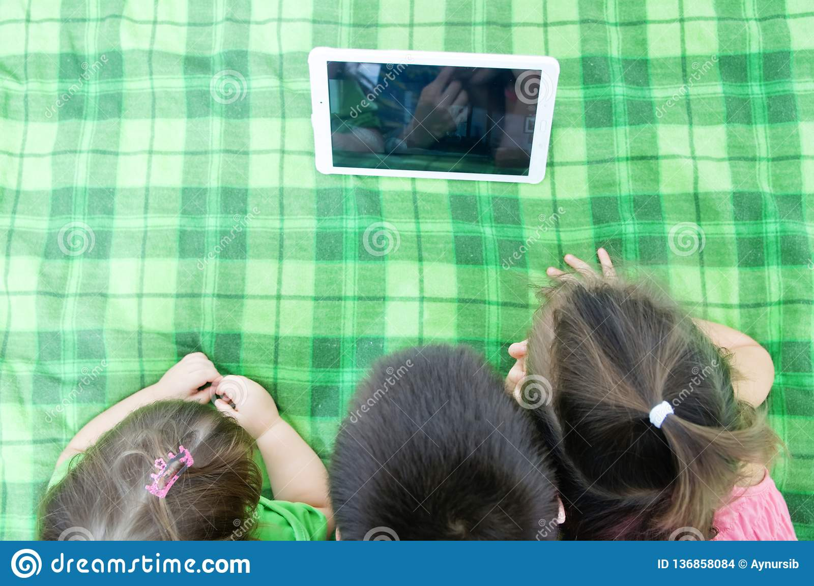 Children looking on pad lying on bed at home. Children time spending. Three kids using tablet