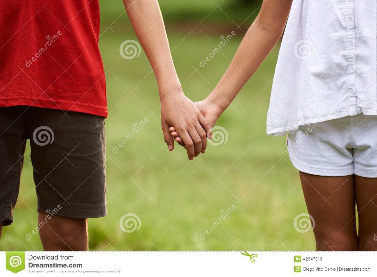 teenage girl holding hands with little girl