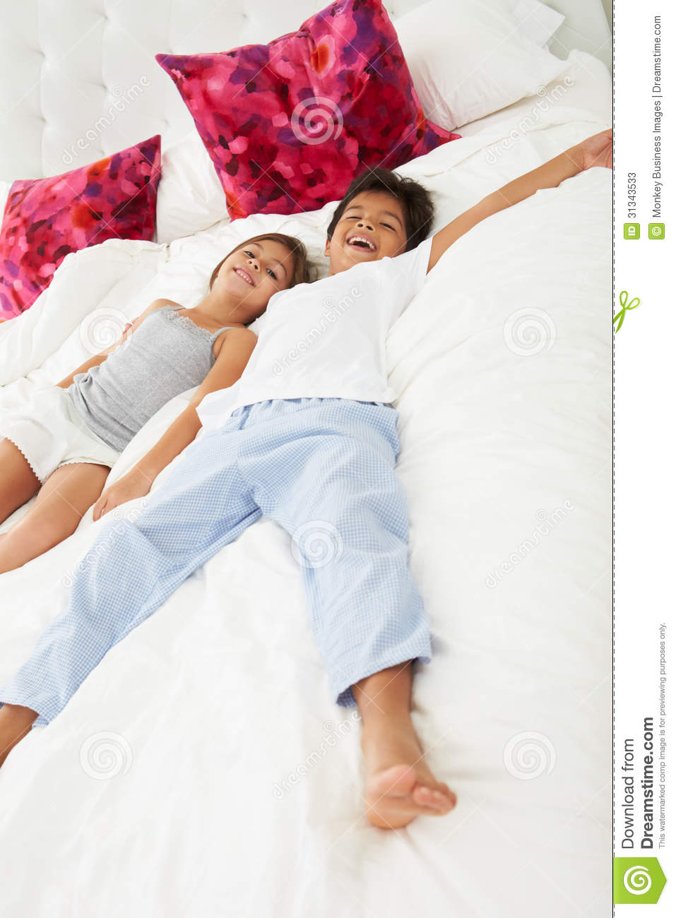 Children lying on bed in pajamas together smiling to camera