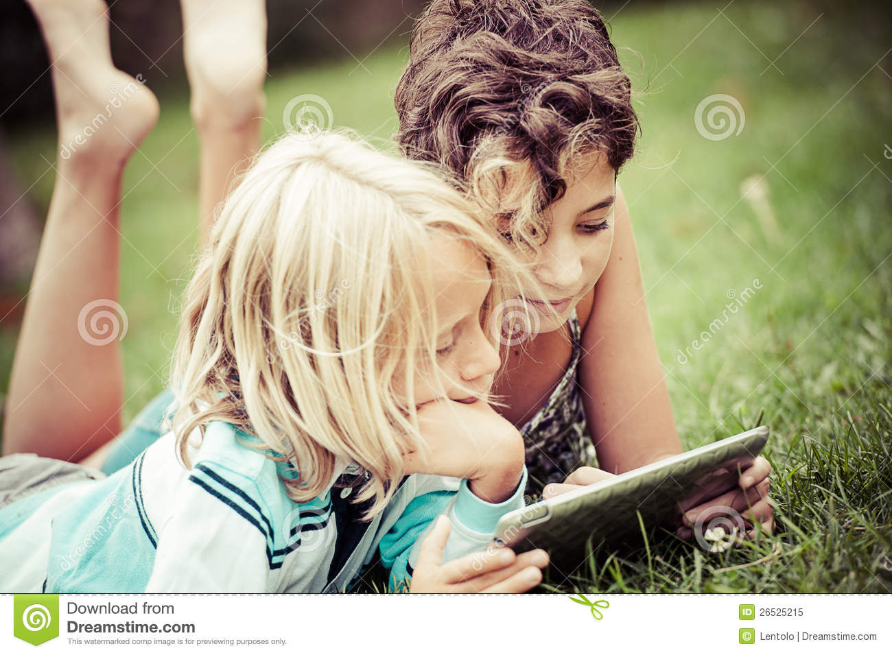 Children lying on the grass looking on the tablet