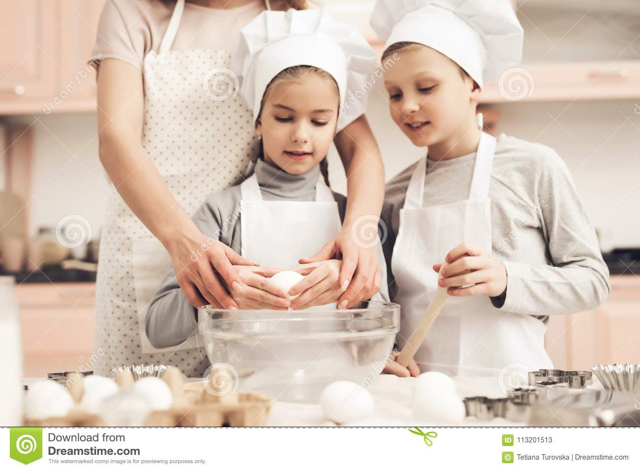 Children with mother in kitchen. Mother is teaching kids how to break eggs.