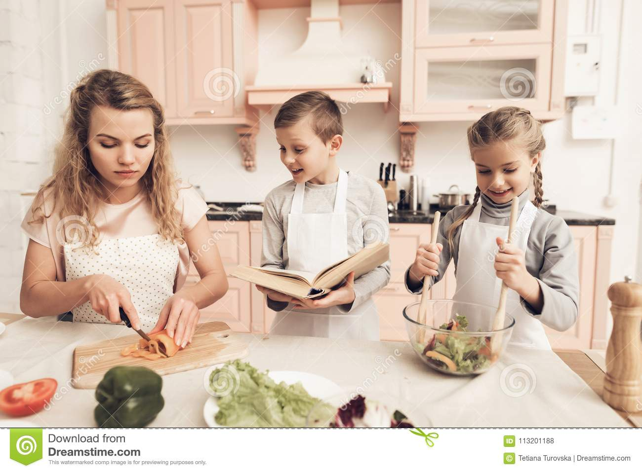Children with mother in kitchen. Kids are helping mother to make salad.