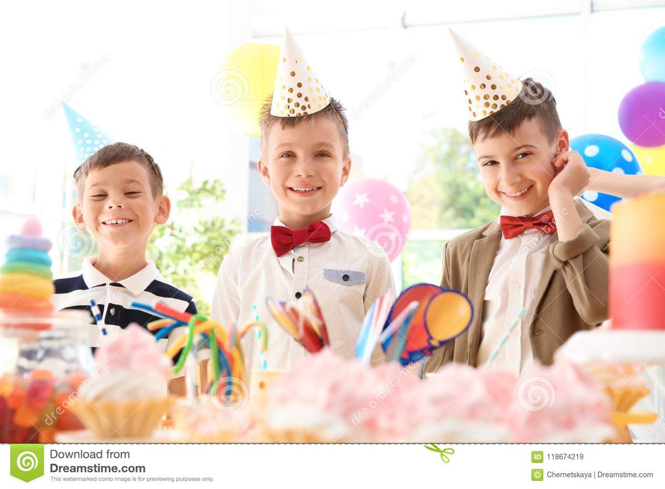Children near table with treats at birthday party indoors
