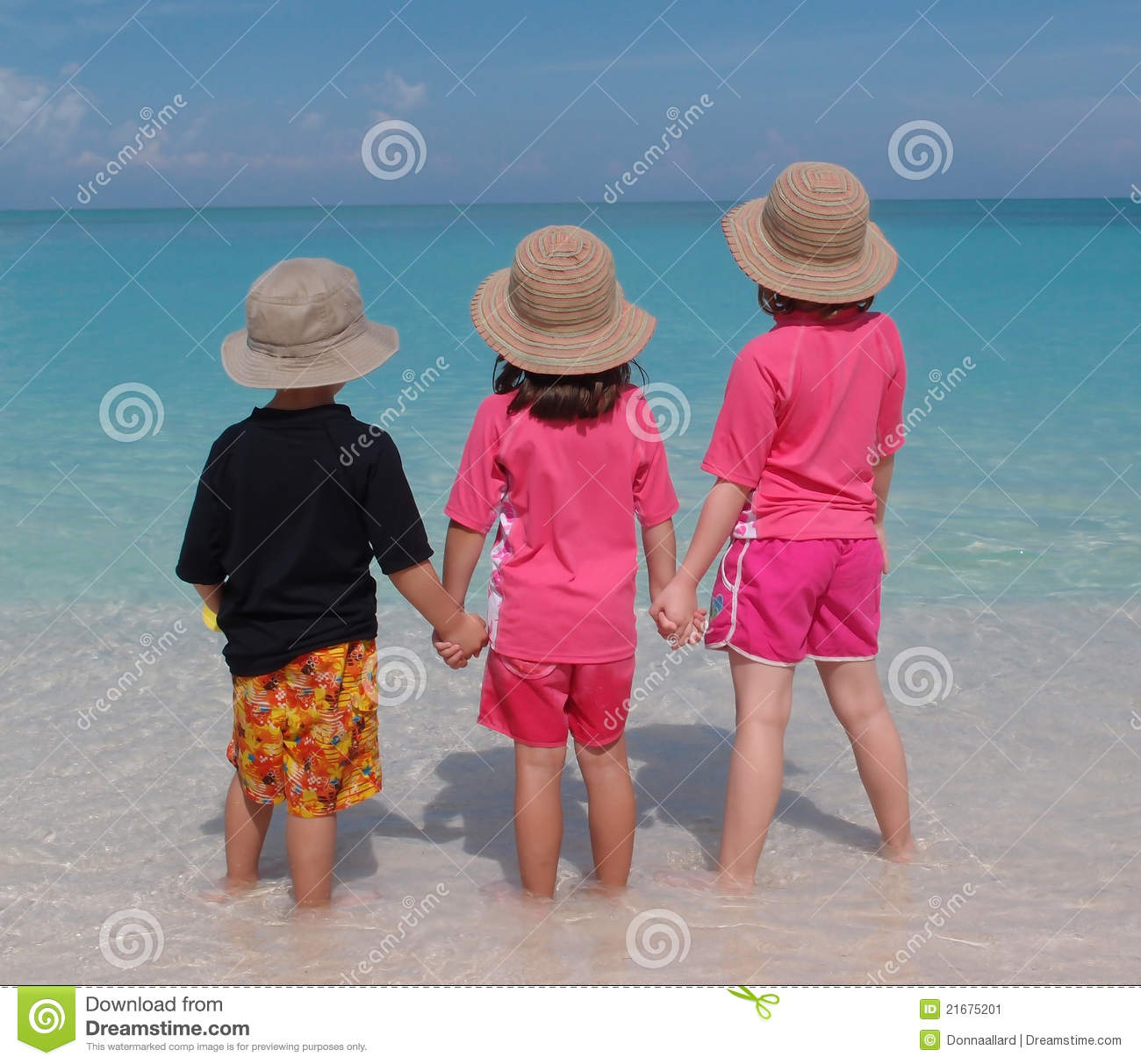 Rear view of three children holding hands and paddling in sea with sun